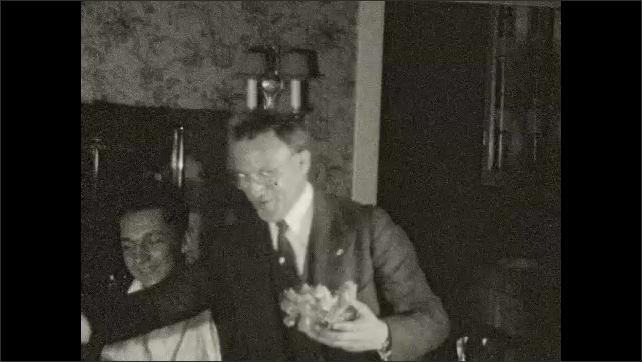 1920s: UNITED STATES: man has fun at table. Man serves food