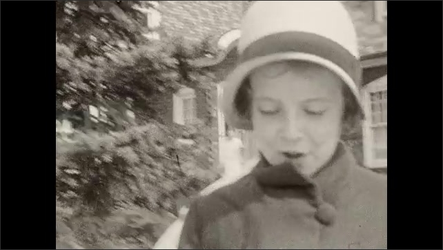 1930s: girl in hat stands near tree, talks and waves hand. girls in coats hold purses and walk down sidewalk near retaining wall, grass and brick house with  large glass windows and doors.