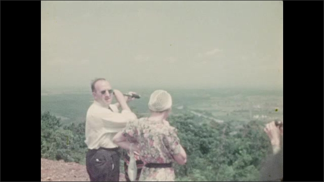 1940s: Two women, man and boy look over cliff with binoculars and telescope.