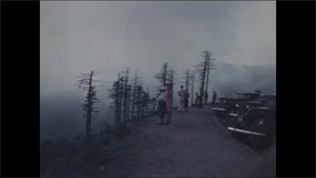 1940s: Clouds on wooded hillside. Cars parked at viewpoint.