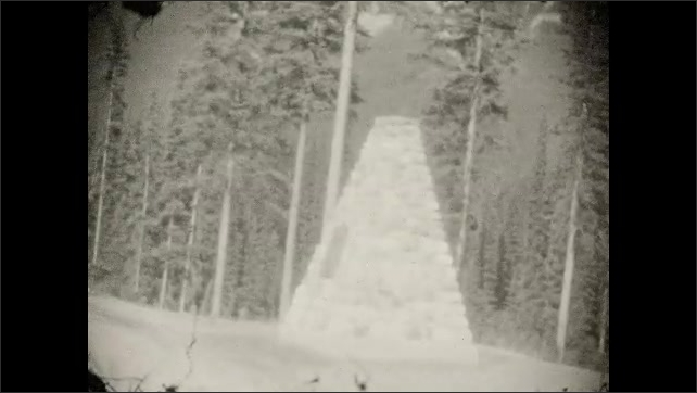 1920s: Driving down road through woods. Memorial structure. Sign at side of road.