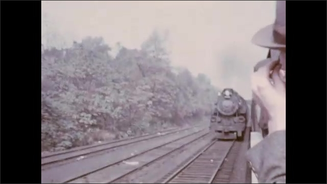 1930s: UNITED STATES: men stand in open air train carriage. Passengers on train journey. Steam train on tracks. Train travels past water