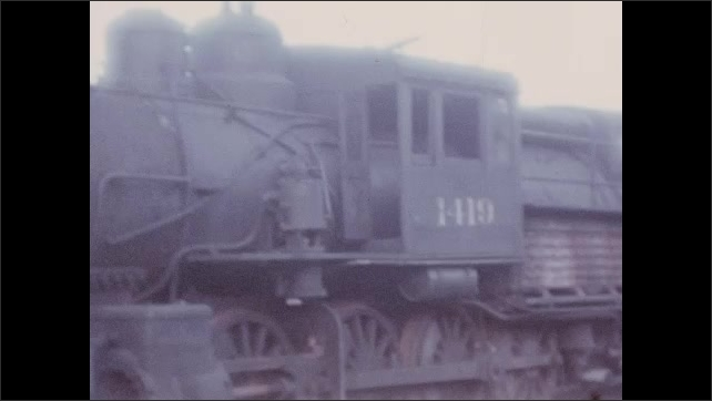 1930s: UNITED STATES: train conductor waves red flag by train. Side view of steam train. Train on tracks