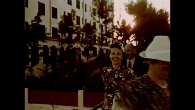 1930s: UNITED STATES: family on hotel veranda before sunset. Lady smiles at camera. Family dressed up for dinner.