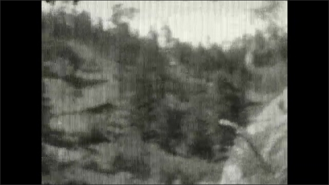 1920s: UNITED STATES: train ride through mountains. Trees by railway. River runs down slope. Man on carriage.