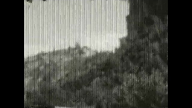 1920s: UNITED STATES: view along valley from window of train. Pylon by railway line. Cliffs by railway lines.