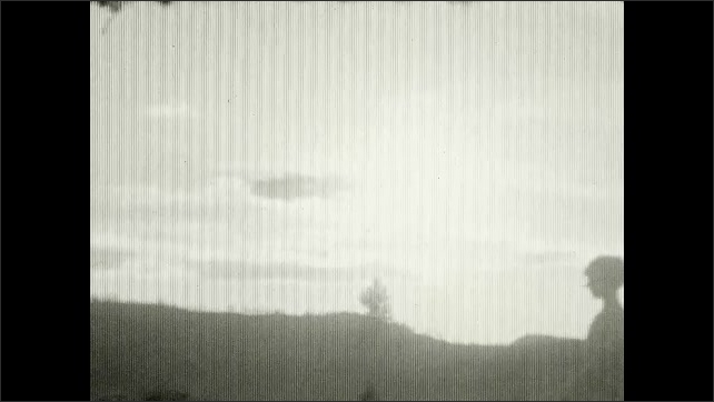 1920s: UNITED STATES: girl and lady on top of hill. View across landscape from top of hill. Outline of girl on hill. Sunset over mountain top