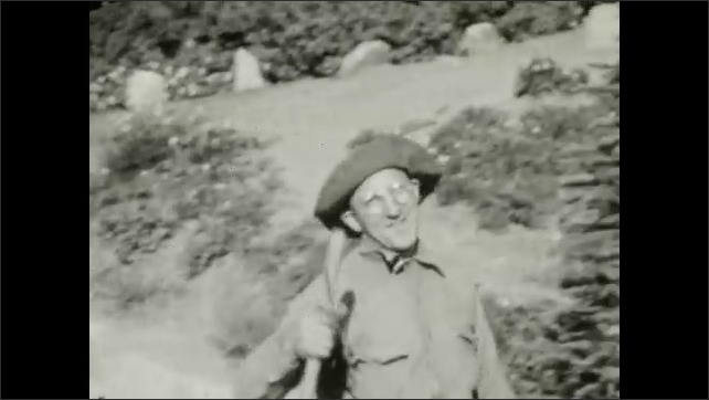 1920s: River rushes down mountainside.  Group of people hike together.  Man walks strangely.  Mountain.