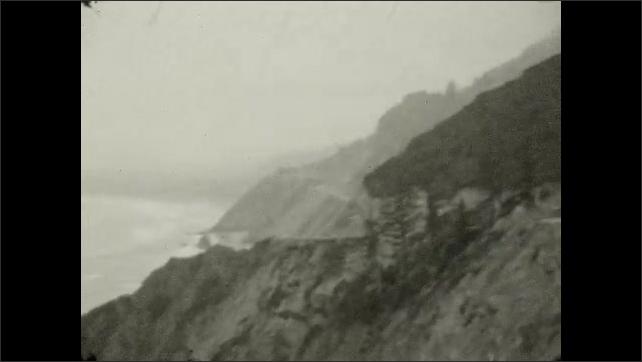 1920s: Mountains.  Winding road.  Beach.  Boulder in water.  Ocean.