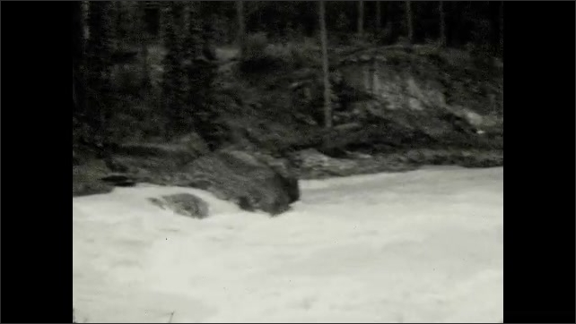 1920s: Woman and girl walk across bridge. Sign for bridge. Water flows over rocks, down river.