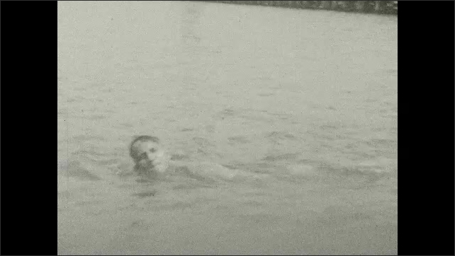 1920s: People walk down beach. Man swims in water.