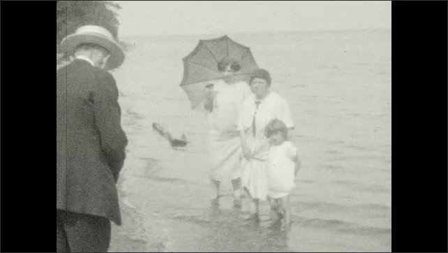 1920s: Beach.  Man takes picture of women and girl wading in water.  People walk along.