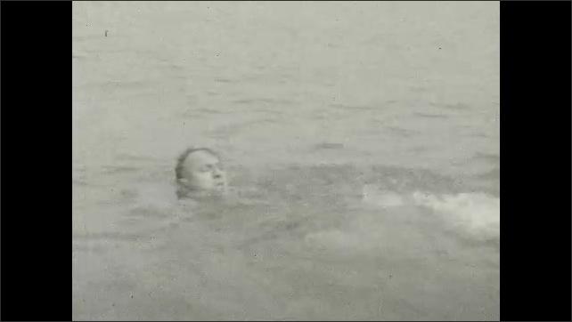 1920s: Man swims in bay.