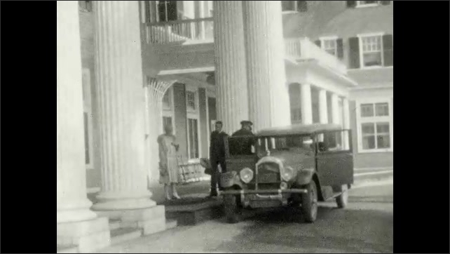 1920s: UNITED STATES: entrance to hotel. Ladies stand by lobby. Valet by car. Car in entry.