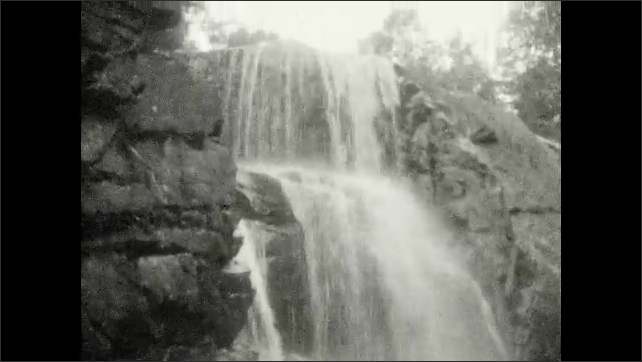 1920s: UNITED STATES: trail through gorge. Waterfall in woods. Water falls over edge of rocks