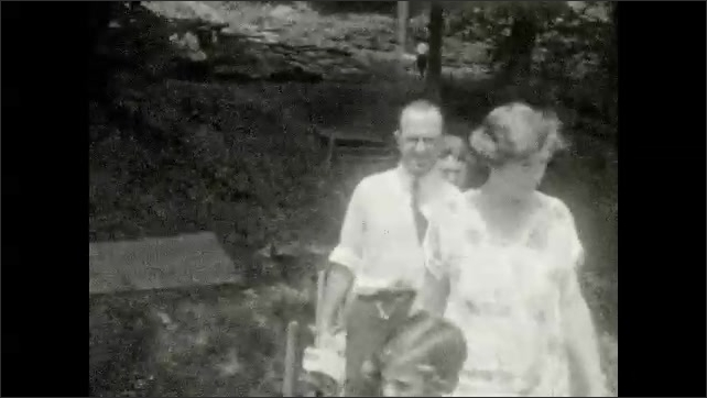 1920s: UNITED STATES: girl walks along path. Family walk by waterfalls. View across valley to building