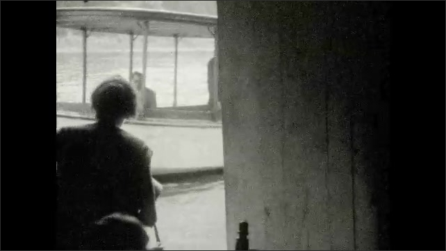 1920s: UNITED STATES: lady in boat. Girl looks at water from window. Family wait for boat to arrive. Family sit on passenger ferry