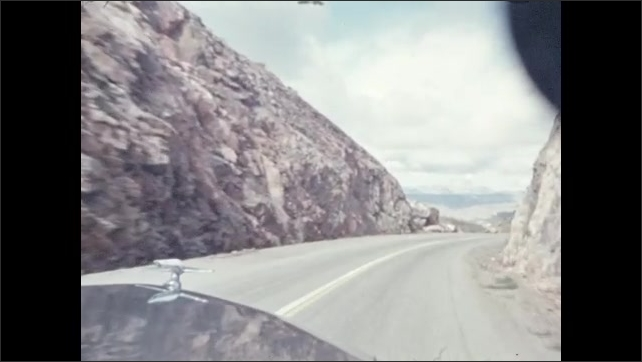 1940s: Deep desert canyon vista. Woman stands at large window.