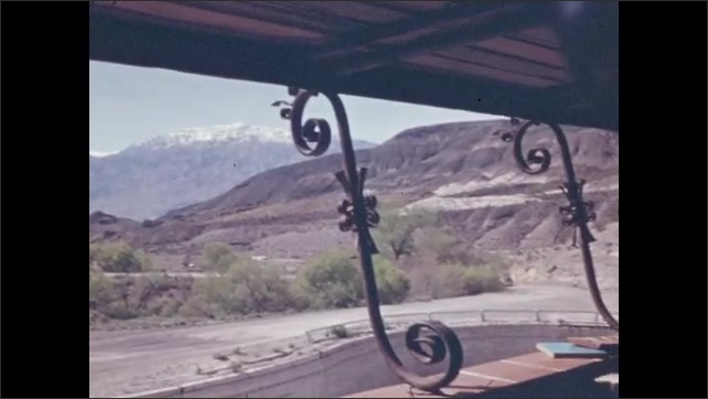 1940s: DEATH VALLEY, UNITED STATES: interior of room. View of mountain landscape through from castle porch. Vines growing on roof of building