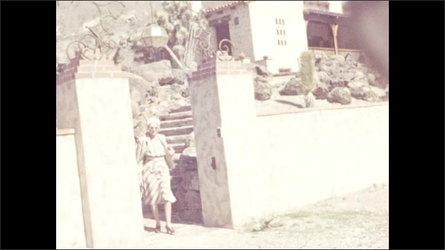 1940s: DEATH VALLEY, UNITED STATES: entrance of house. Lady walks down steps. House and garden. Veranda and arches