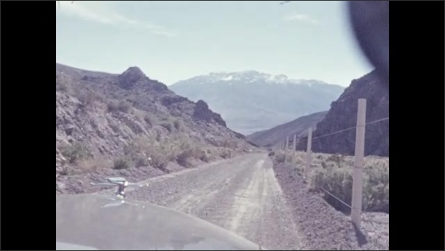 1940s: DEATH VALLEY, UNITED STATES: view along road through Death Valley. Fence by road. Dusty track. Rocky landscape. Lady looks at view.