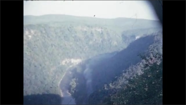 1940s: Steam train runs along canyon river. Men and women look out over mountain vista. Mountains and trees.