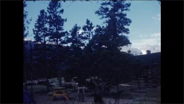 1940s: Bottle stands on the top of car, trees in background. Car parked at picnic park with tables and trees, house made of wood with mountains in background and a small road.