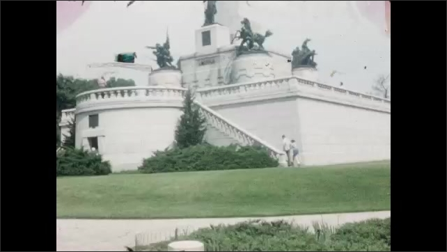 1940s: Bust of Abraham Lincoln. Metal plaque on statue pedestal. People climb steps of large memorial building. People walk around large memorial building and obelisk.