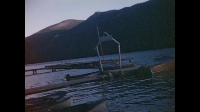 1940s: UNITED STATES: view across lake. Boats and jetty by lake. People by boats. Trees around lake. Mountain reflection in water.