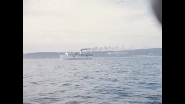 1940s: Steam ship moves along lake. Motor boat speeds across lake. Homes and buildings on lakeshore. Flag waves in breeze on lake.