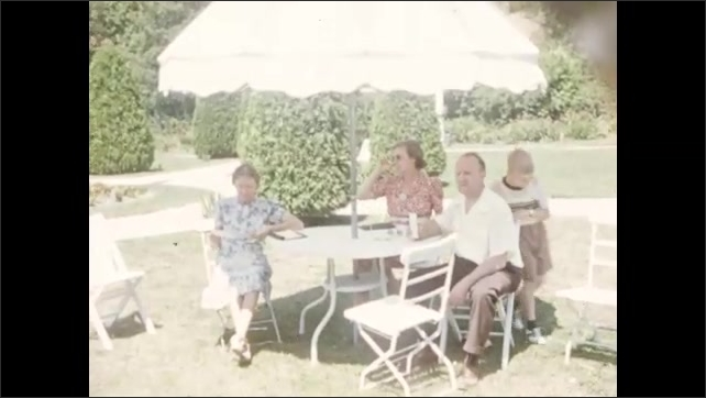 1940s: Family sits at umbrella table on lawn. Boy walks around table and waves. Flagpole and lawn furniture. Lake and trees panorama.
