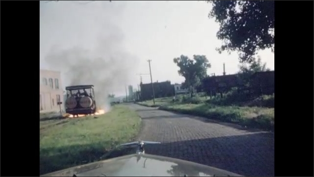 1940s: Car drives down cobblestone road. Vehicle in grass burns grass with fire. Car drives into city.