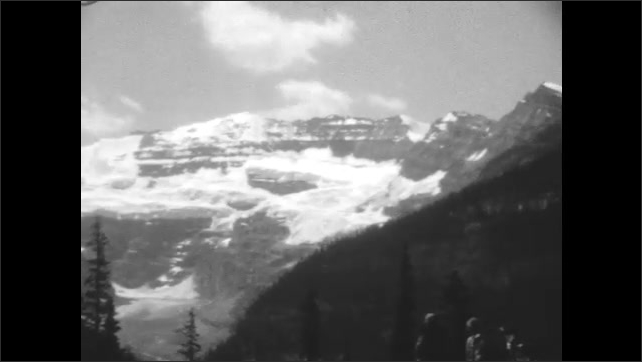 1920s: Brief view of cabin. British flag blowing in breeze. Snow-capped mountains, cloudy sky, and lake in valley. Women in jackets looking at view. Women walk toward large brick building.