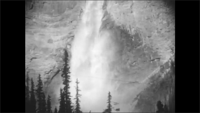 1920s: Woman and girl on edge of river. Waterfall rushing down from top of nearby mountain.