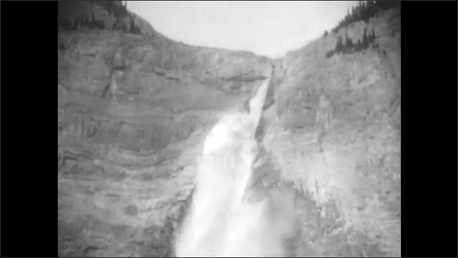 1920s: Water with trees and mountains. Waterfall rushing down side of mountain.