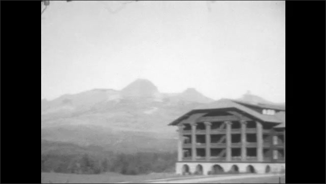 1920s: UNITED STATES: ranch in valley. Mountains on horizon. Buildings and visitor center