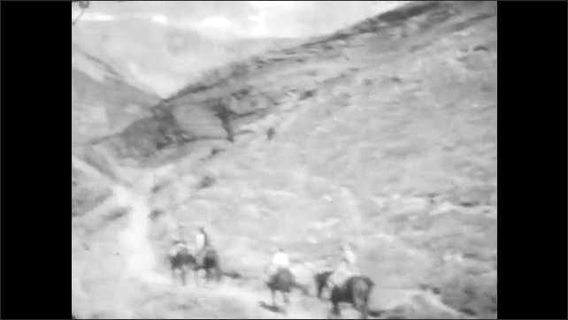 1920s: People ride horses in the mountains. Mountains in background.