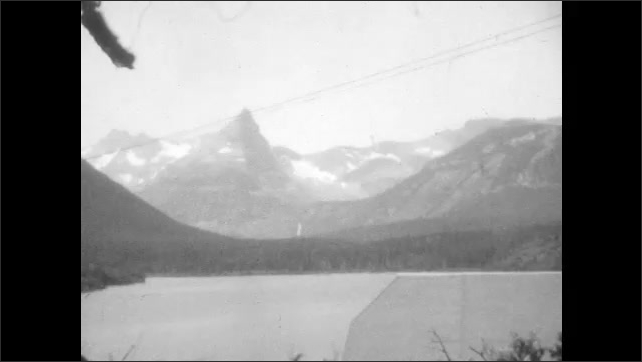 1920s: Vignette view of rock. Woman and child hike and point to somewhere out of view. Lake with mountains in background.