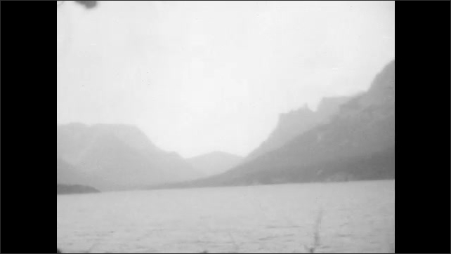1920s: women sit on benches on boat and look out at lake, forests and mountains.