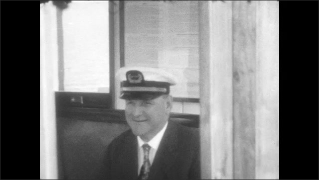 1920s: mountains slope into lake. Woman steers wheel on boat. man in captain uniform sits on bench and smiles.