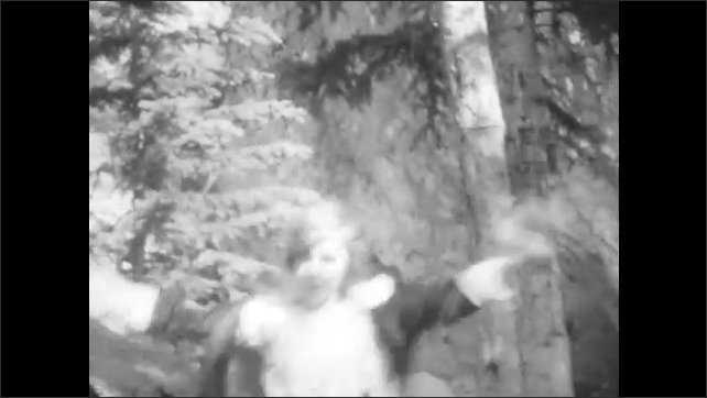 1920s: woman and girl walk down hilly trail through woods in mountain range.