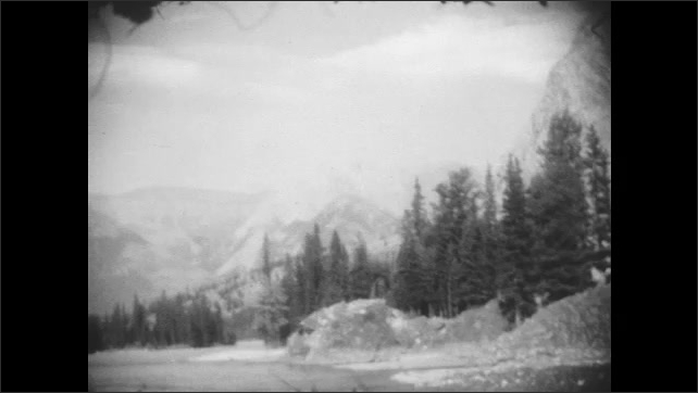 1920s: water flows past trees and rocky mountain pass.