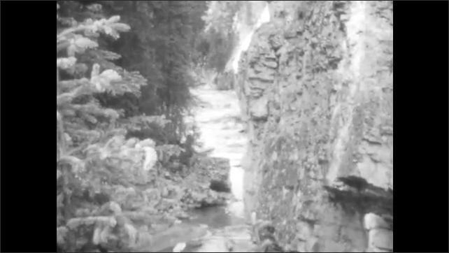 1920s: water falls from beneath bridge. woman walks on dock to boat on lake. stream flows down rocky mountain passage into rapids near pine trees.