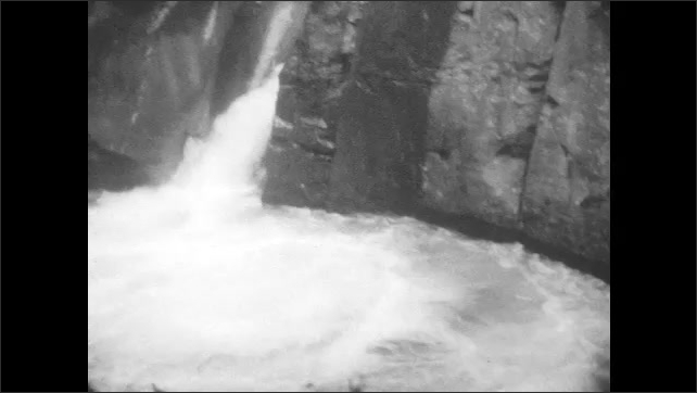 1920s: stream rushes into rapids near cliff face with pine trees. waterfalls drop by dark cavern, down rocky mountain passages and below men, woman, boy and girl on wood bridges.