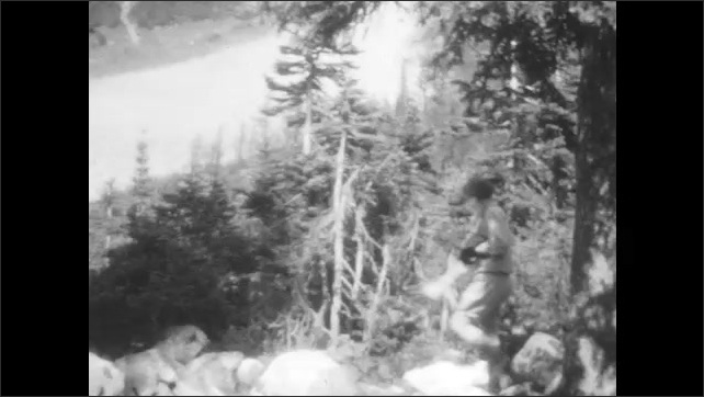 1920s: bench sits next to lake in front of snow-capped mountain. men and women in sweaters walk along trail with rocks and boulders through forest.