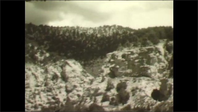 1930s: Forest path through trees. Film leader. Rocky cliff face with trees. Forest valley. Trail down rocky hillside of trees. Two people high on roadside hill.