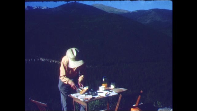 1940s: Pink wildflowers by roadside, mountain landscape, man and boy stand at table preparing meal, sit and eat.