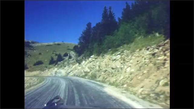 1940s: Mountain landscape, man and boy sit at table, eat. Driving down winding mountain road, no guardrails.