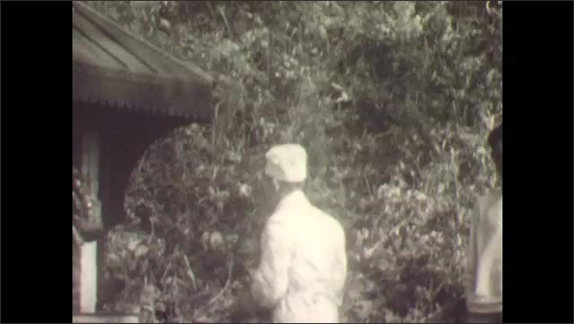1930s: Men in white uniforms and chef's hats cook outside by large outdoor grill.
