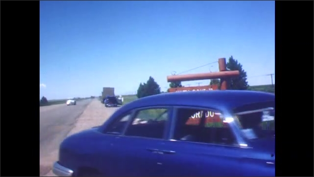 1940s: Man stands behind Welcome to Colorado sign, walks under sign, stumbles. Cars pull off to the side of the road. Car drives down road, past train.